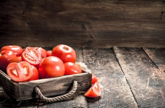 Frische tomaten auf einem tablett. auf einem hölzernen hintergrund.