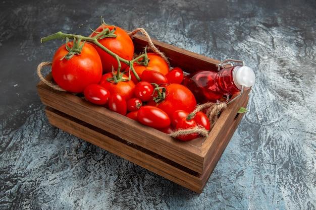 Frische tomaten der vorderansicht mit kirschen innerhalb der schachtel