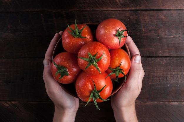 Frische tomaten in den händen auf hölzernem. tomaten ernten. ansicht von oben