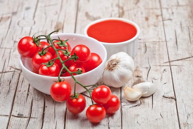 Frische tomaten in der weißen schüssel, in der soße und im rohen knoblauch auf rustikalem holztisch.