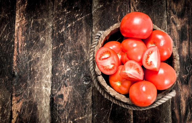 Frische tomaten in einem holzeimer. auf einem hölzernen hintergrund.