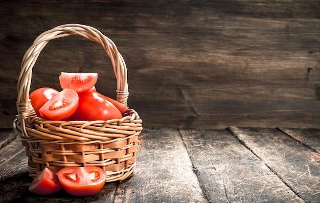 Frische tomaten in einem korb. auf einem hölzernen hintergrund.