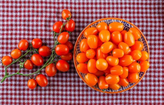 Frische tomaten in einem teller auf einem picknicktuch. flach liegen.