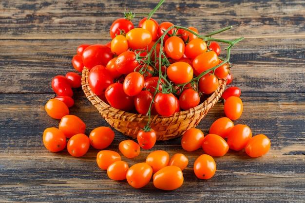 Frische tomaten in einem weidenkorb auf einem holztisch.