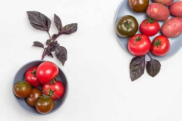 Frische tomaten in grauer schüssel und auf teller. zweige von blauem basilikum. weißer hintergrund. platz kopieren. flach legen
