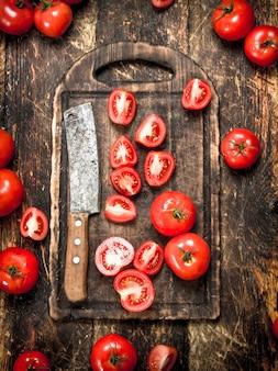 Frische tomaten mit altem beil auf einem schneidebrett auf hölzernem hintergrund