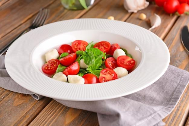 Frische tomaten mit basilikum und mozzarella auf teller