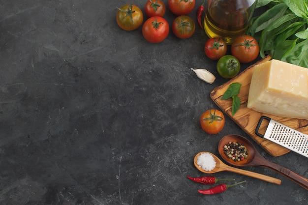 Frische tomaten mit draufsicht der gewürze und des käses über dunklen beton