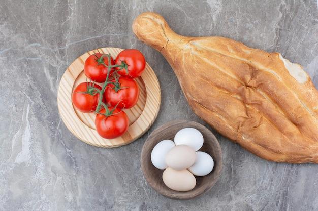 Frische tomaten mit eiern und brot auf marmorhintergrund. foto in hoher qualität