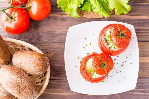 Frische tomaten mit käse und ei gebacken mit frühlingszwiebeln bestreut