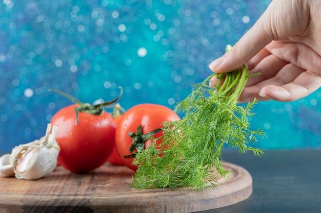 Frische tomaten mit knoblauch auf einem holzbrett.