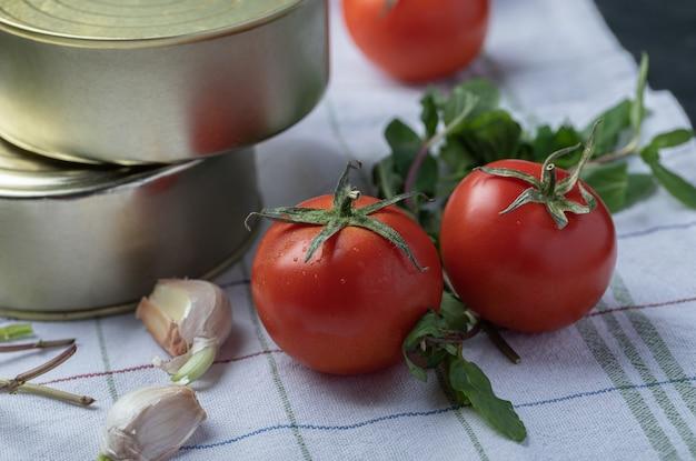 Frische tomaten mit knoblauch und grüns auf einer tischdecke.