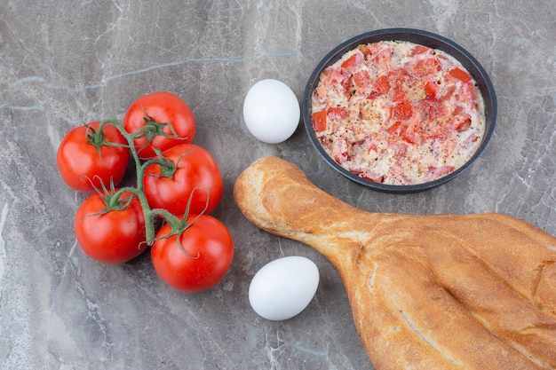 Frische tomaten mit spiegeleiern und brot auf marmorhintergrund. foto in hoher qualität