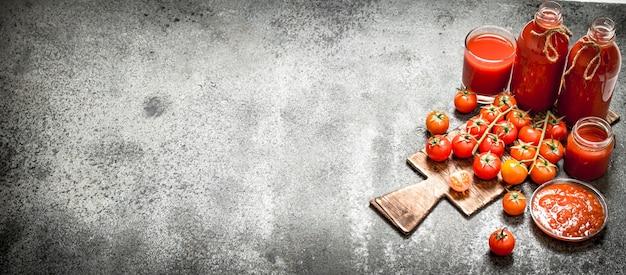 Frische tomaten, tomatensaft und sauce. auf rustikalem tisch.