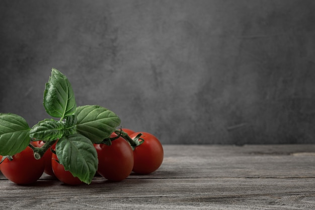 Frische tomaten und basilikumkraut auf einem alten holztisch. dunkler hintergrund.