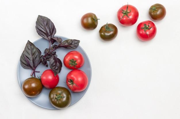 Frische tomaten und zweige des blauen basilikums auf dem teller. tomaten auf dem tisch. weißer hintergrund. platz kopieren. flach legen