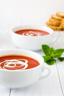 Frische tomatensuppe in der weißen schale auf weißem holztisch