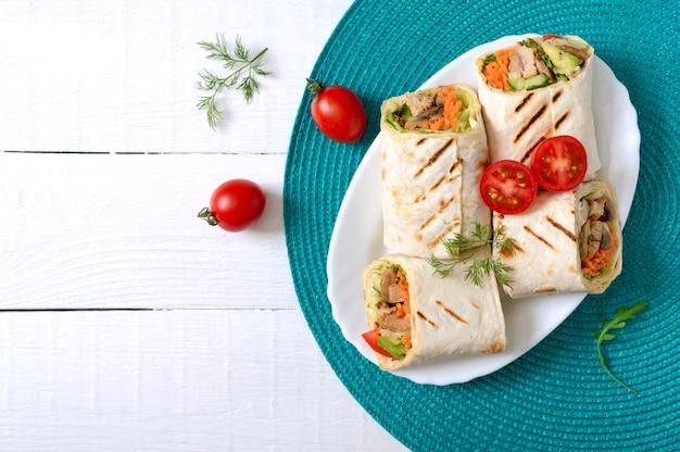 Frische tortilla wraps mit hühnchen, pilzen und frischem gemüse. mexikanischer burrito des huhns. leckere vorspeise. gerichte aus fladenbrot. gesundes lebensmittelkonzept
