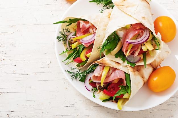 Frische tortillaverpackungen mit fleisch und gemüse auf platte