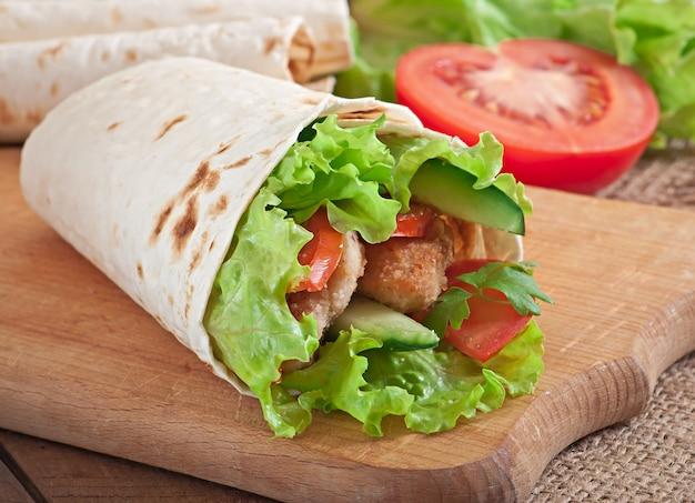 Frische tortillaverpackungen mit hühnernuggets und gemüse auf platte