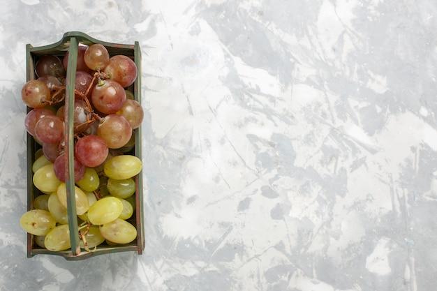 Frische trauben der draufsicht innerhalb des hölzernen schreibtisches auf dem weißen hintergrundfrucht milde saftige frische