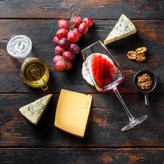 Frische trauben, rotwein, französischer käse, honig und nüsse über rustikalem verwittertem holz. ansicht von oben mit quadratischer ernte.