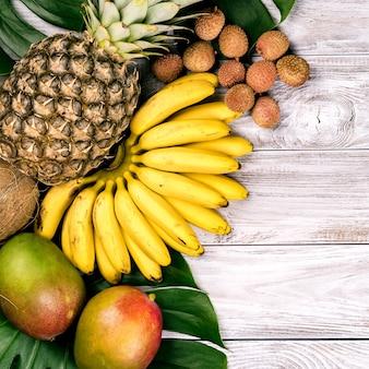 Frische tropische frucht auf holz draufsicht. bananen, ananas, kokosnuss, mango, litschi, kastanien.