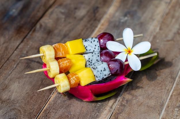 Frische tropische früchte auf spießen in weißer platte - gesundes frühstück, gewichtsverlustkonzept. thailand. nahaufnahme
