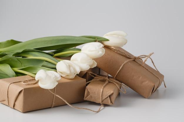 Frische tulpen und geschenkbox über weißer oberfläche