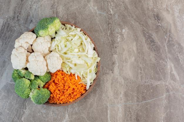 Frische und appetitliche salatzutaten, zubereitet und auf einem holztablett auf marmor ausgestellt.