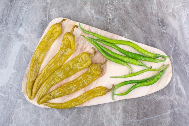Frische und fermentierte paprika auf holzbrett.