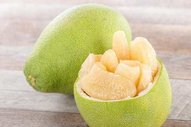 Frische und geschälte pampelmuse (schellfisch), grapefruit mit scheiben auf hölzernem tischhintergrund