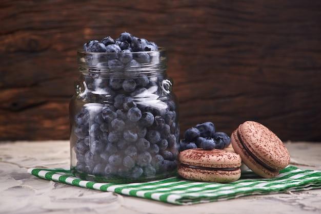 Frische und geschmackvolle blaubeerbeeren in einem glasgefäß auf einer karierten serviette mit süßen makronen