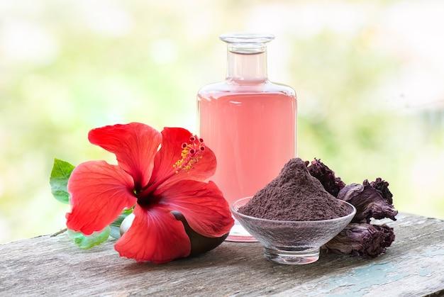 Frische und getrocknete hibiskusblüte, pulver und wasser aus getrockneten blütenblättern auf natürlichem.