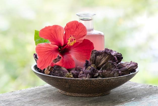 Frische und getrocknete hibiskusblüte und wasser aus getrockneten blütenblättern auf natürlichem.