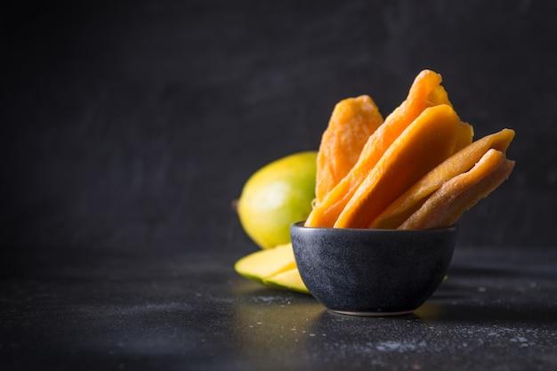 Frische und getrocknete mangochips auf schwarzem