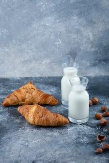 Frische und leckere croissants mit gesunden haselnüssen in schale und milch.