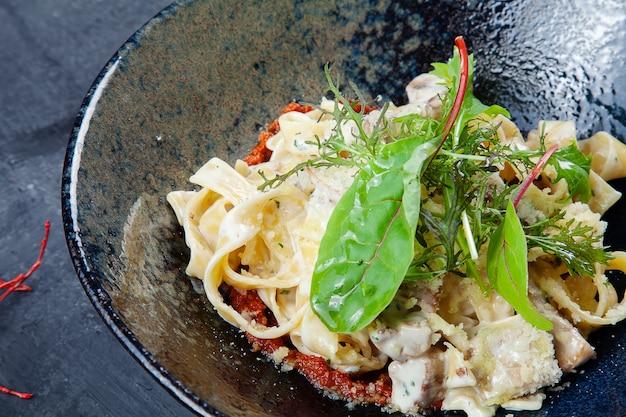 Frische und leckere hausgemachte italienische pasta mit basilikum, tomate und pilz in dunkler schüssel. italienische küche. lebensmittelfotohintergrund mit kopienraum.