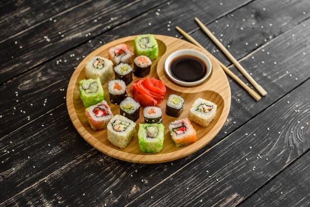 Frische und leckere sushi auf dunklem hintergrund. es kann als hintergrund verwendet werden