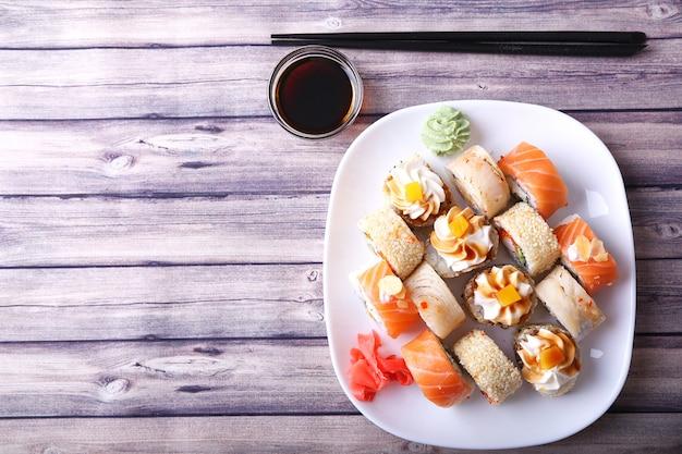 Frische und leckere traditionelle japanische sushi-rollen auf weißem teller. draufsicht