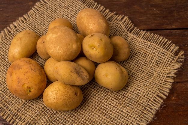Frische und rohe kartoffeln gestapelt auf holztisch