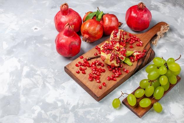 Frische und saftige früchte des roten granatapfels der vorderansicht mit trauben auf weißem schreibtisch