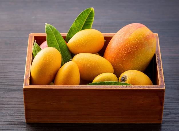 Frische und schöne mangofrucht gesetzt in einer holzkiste auf einem dunklen hölzernen hintergrund, kopienraum (textraum), leer für text