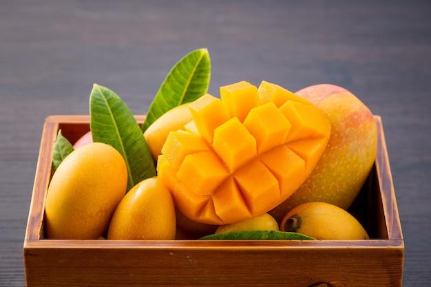 Frische und schöne mangofrucht, gesetzt in einer holzkiste mit geschnittenen geschnittenen mangostücken auf einem dunklen hölzernen hintergrund, kopierraum (textraum), leer für text