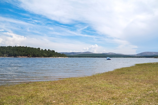 Frische und sommerliche landschaft mit einem großen fluss inmitten der natur und einer kleinen yacht mitten im wasser.