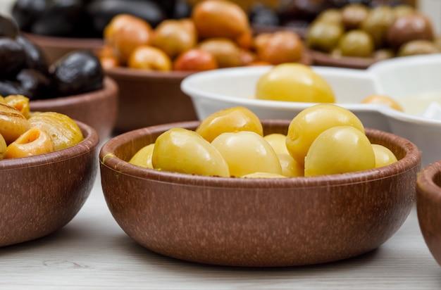 Frische und verschiedene oliven in ton und weißen schalen auf weißem holz. seitenansicht.