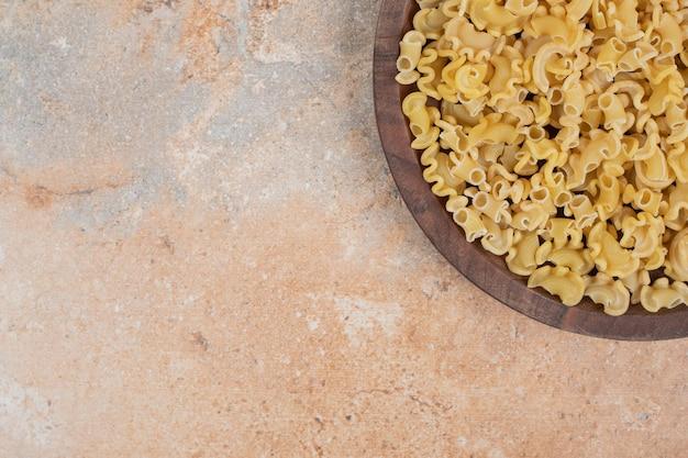 Frische ungekochte makkaroni auf holzbrett auf marmorfläche
