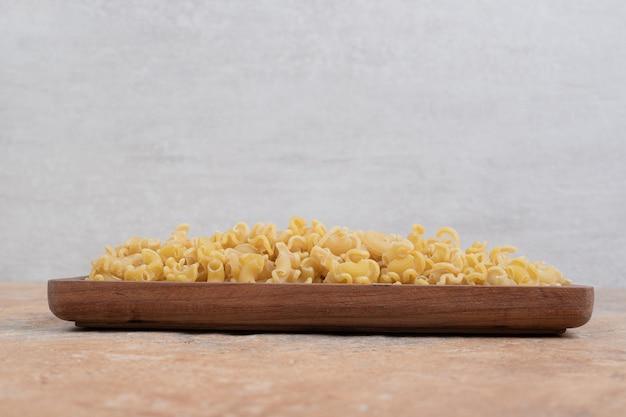 Frische ungekochte makkaroni auf holzschale auf marmorfläche