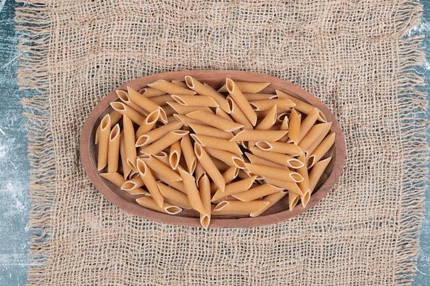 Frische ungekochte makkaroni auf holzschale auf sackleinen.