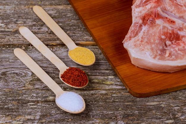 Frische ungekochte schweinekoteletts auf einer schieferplatte, kräutern und gewürzen